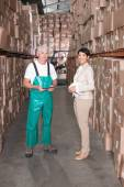 Warehouse worker and manager smiling at camera — Stock Photo