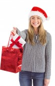 Festive blonde holding christmas gift and bag — Stock Photo