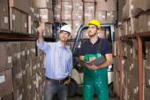 Warehouse manager talking with forklift driver — Stockfoto