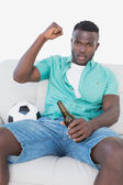 Soccer fan cheering while watching tv — Stockfoto