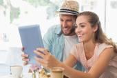 Happy couple enjoying coffee using tablet — Stock Photo