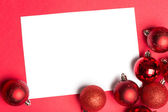 White page with red christmas baubles — Stock fotografie