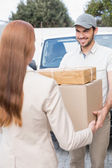 Delivery driver passing parcels to customer — Stock Photo