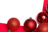 White page with red christmas baubles — Stockfoto