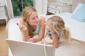 Girl and mother on bed using laptop — Stock Photo