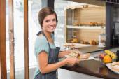 Pretty waitress holding plate of food — Foto de Stock