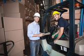 Warehouse manager talking with forklift driver — Stok fotoğraf