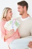 Young man carrying cheerful woman with banknotes — Stock Photo