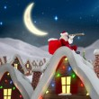 Composite image of santa sitting on roof of cottage — Stock Photo #56886711