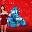 Pretty girl in santa outfit holding gift — Stock Photo #56889147