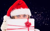 Composite image of festive blonde holding a gift — Stock Photo