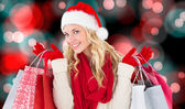 Happy festive blonde with shopping bags — Stock Photo