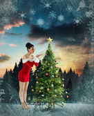 Pretty santa girl blowing over her hands — Stock Photo