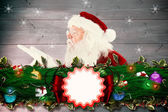 Composite image of santa claus blowing — Stock Photo