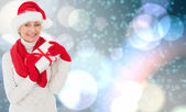Composite image of festive woman holding gift — Stock Photo