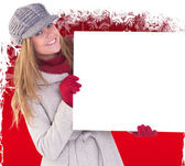 Happy blonde in winter clothes showing card — Stock Photo
