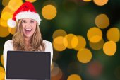 Composite image of festive blonde showing a laptop — Stock Photo