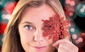 Composite image of festive blonde holding a snowflake — Stock Photo