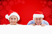 Festive couple showing poster — Stock Photo