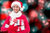 Composite image of festive brunette holding gifts — Stock Photo