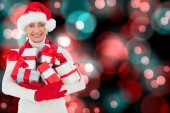 Composite image of festive woman holding gifts — Stock Photo
