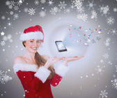 Pretty girl in santa costume holding hand out — Stock Photo