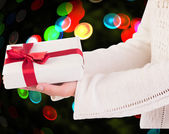Composite image of woman offering a gift box — Stock Photo