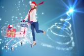 Festive blonde pushing trolley full of gifts — Stock Photo