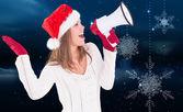 Festive blonde shouting through megaphone — Stock Photo