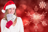 Composite image of festive blonde showing fan of dollars — Stock Photo