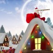 Composite image of santa sitting on roof of cottage — Stock Photo #56891339