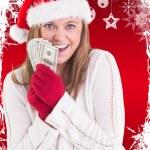 Festive blonde showing fan of dollars — Stock Photo #56892783