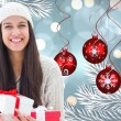 Composite image of festive brunette holding gifts — Stock Photo #56894065