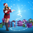 Pretty girl in santa costume holding hand out — Stock Photo #56894531