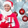 Composite image of festive brunette holding gifts — Stock Photo #56895005