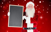 Composite image of santa claus showing blackboard — Stock Photo