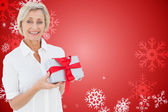 Composite image of mature woman holding gift — Stock Photo