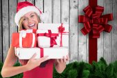 Composite image of festive blonde holding pile of gifts — Stock Photo