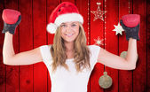 Composite image of festive blonde with boxing gloves — Stock Photo