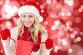 Happy festive blonde with shopping bag — Stockfoto