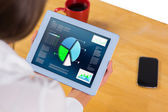 Composite image of businesswoman using tablet at desk — Stockfoto