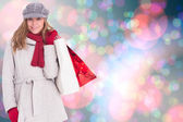 Happy blonde in winter clothes with bags — Stock Photo
