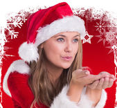 Composite image of festive blonde blowing over hands — Stock Photo