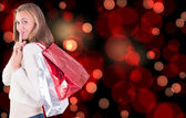 Pretty blonde keeping a secret holding bags — Stock Photo