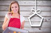 Pretty homemaker showing hot cookies — Stock Photo