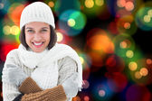 Composite image of brunette in warm clothing — Stock Photo