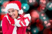 Composite image of festive brunette holding gift — Stock Photo