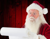 Composite image of santa claus checking his list — Stock Photo