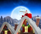 Composite image of santa sitting on roof of cottage — Stock Photo