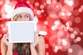 Composite image of festive blonde showing a tablet — Stock Photo
